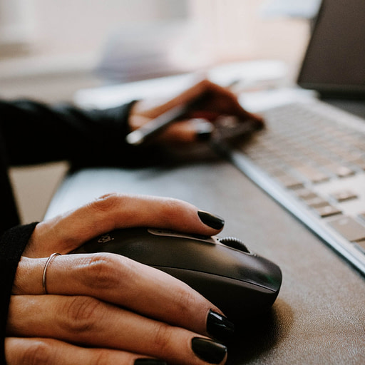 Person working at computer. One hand on keyboard and the other on the mouse.