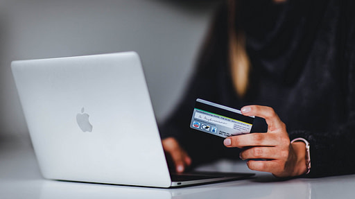 Woman at open laptop holding credit card