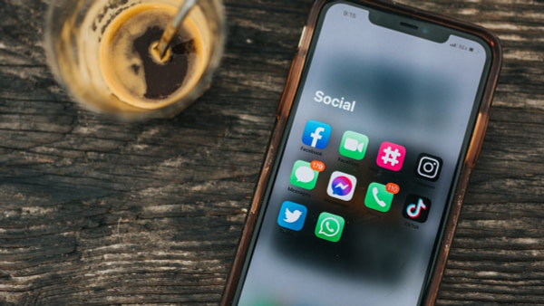 Phone showing social media apps on table next to drink