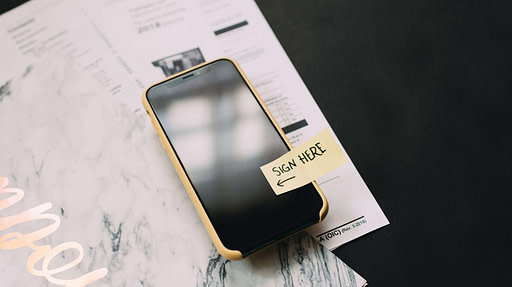 Phone Sitting on a desk with papers, sticky note tab saying 'sign here' on phone